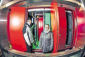 Foto: Prof. Gregor Engels (Vorstand SICP/Uni Paderborn) und Prof. Gudrun Oevel (Leiterin des Zentrums für Informationstechnologien der Uni Paderborn) vor einem der vier IT-Sicherheitsschränke im Windrad-Turm in Asseln.